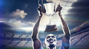 Composite image of happy sportsman looking up while holding trophy. Happy sportsman looking up while holding trophy against rugby stadium royalty free stock photos