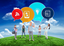 Composite image of happy students with speech bubbles Royalty Free Stock Photos
