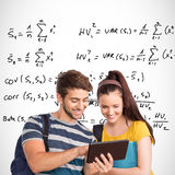 Composite image of happy students using tablet pc Royalty Free Stock Photography
