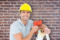 Composite image of happy technician holding drill machine while leaning on ladder Royalty Free Stock Photography