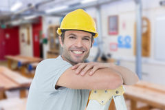 Composite image of happy technician leaning on step ladder Royalty Free Stock Photos