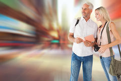 Composite image of happy tourist couple using the guidebook Royalty Free Stock Photo