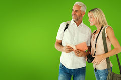 Composite image of happy tourist couple using the guidebook Stock Photos
