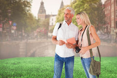 Composite image of happy tourist couple using the guidebook Stock Photo