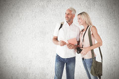 Composite image of happy tourist couple using the guidebook Royalty Free Stock Image