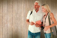 Composite image of happy tourist couple using the guidebook. Happy tourist couple using the guidebook against wooden planks royalty free stock photography