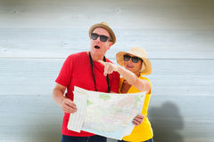 Composite image of happy tourist couple using map Stock Photography