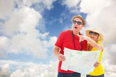 Composite image of happy tourist couple using map Stock Image