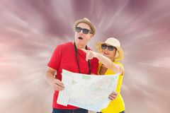 Composite image of happy tourist couple using map Royalty Free Stock Images