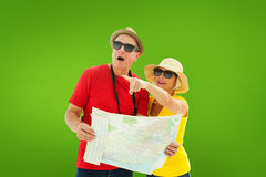 Composite image of happy tourist couple using map Stock Images
