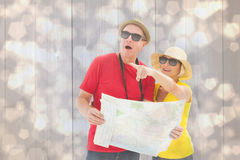 Composite image of happy tourist couple using map Stock Photos