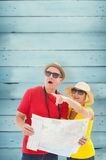 Composite image of happy tourist couple using map. Happy tourist couple using map against wooden planks Stock Photo