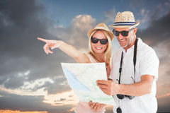 Composite image of happy tourist couple using map and pointing Royalty Free Stock Photo