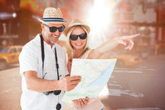 Composite image of happy tourist couple using map and pointing Royalty Free Stock Images