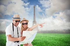 Composite image of happy tourist couple using map and pointing. Happy tourist couple using map and pointing against eiffel tower Stock Photo