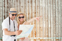 Composite image of happy tourist couple using map and pointing Stock Photos