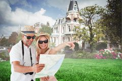 Composite image of happy tourist couple using map and pointing Stock Photography