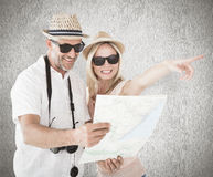Composite image of happy tourist couple using map and pointing Royalty Free Stock Photography