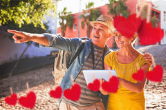 Composite image of happy tourist couple using tablet pc in the city. Happy tourist couple using tablet pc in the city against hearts hanging on a line Stock Photos