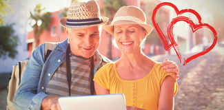 Composite image of happy tourist couple using tablet pc in the city Royalty Free Stock Photography