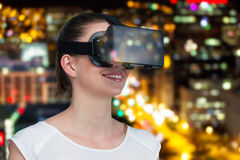 Composite image of happy woman experiencing virtual reality headset. Happy woman experiencing virtual reality headset against defocused image of illuminated Stock Photography
