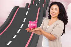 Composite image of happy woman holding a piggy bank Stock Photography