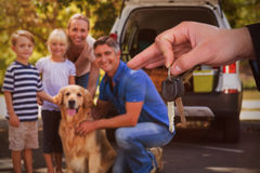 Composite image of happy woman receiving car keys. Happy women receiving car keys against family with dog by car on road Royalty Free Stock Photo