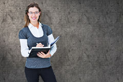 Composite image of happy woman writing in diary Royalty Free Stock Images