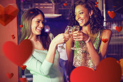 Composite image of happy women toasting champagne glasses. Happy women toasting champagne glasses against love heart pattern Royalty Free Stock Photos