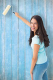 Composite image of happy young brunette painting with roller Stock Photography