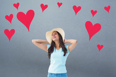 Composite image of happy young brunette wearing sunhat Stock Photography