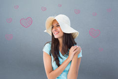 Composite image of happy young brunette wearing sunhat Royalty Free Stock Image