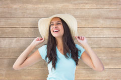 Composite image of happy young brunette wearing sunhat Stock Images