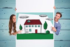 Composite image of happy young couple with blank board Stock Photography