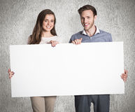 Composite image of happy young couple with blank board Royalty Free Stock Photo