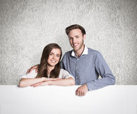 Composite image of happy young couple with blank board Royalty Free Stock Photos