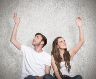 Composite image of happy young couple with hands raised Royalty Free Stock Photo