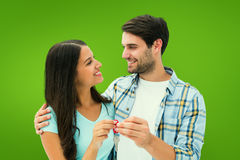 Composite image of happy young couple holding new house key Royalty Free Stock Photography