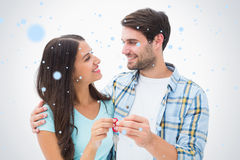 Composite image of happy young couple holding new house key Stock Photo