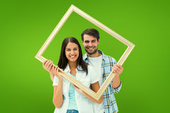 Composite image of happy young couple holding picture frame Stock Photos