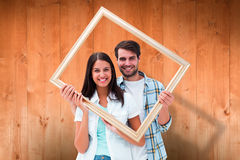 Composite image of happy young couple holding picture frame Royalty Free Stock Images
