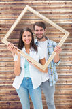 Composite image of happy young couple holding picture frame Stock Image