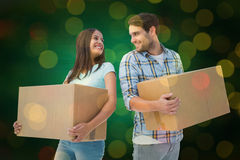 Composite image of happy young couple with moving boxes Royalty Free Stock Photo