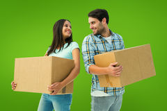 Composite image of happy young couple with moving boxes Stock Images