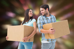 Composite image of happy young couple with moving boxes Stock Photos