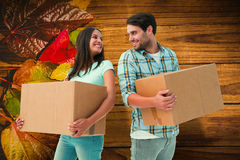 Composite image of happy young couple with moving boxes Stock Photo
