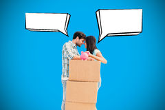 Composite image of happy young couple with moving boxes and piggy bank Stock Image