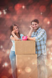 Composite image of happy young couple with moving boxes and piggy bank Stock Photography