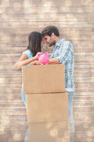 Composite image of happy young couple with moving boxes and piggy bank Royalty Free Stock Photo