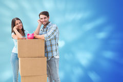 Composite image of happy young couple with moving boxes and piggy bank Stock Photo